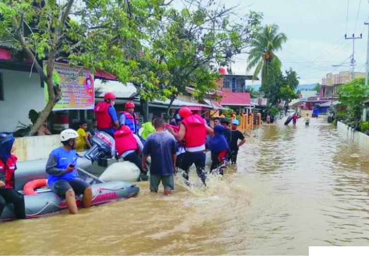 Petugas dari berbagai instansi dan lembaga yang memberikan bantuan kepada warga yang menjadi korban banjir di Kota Solok, Rabu (12/01/2021). LANGGAM