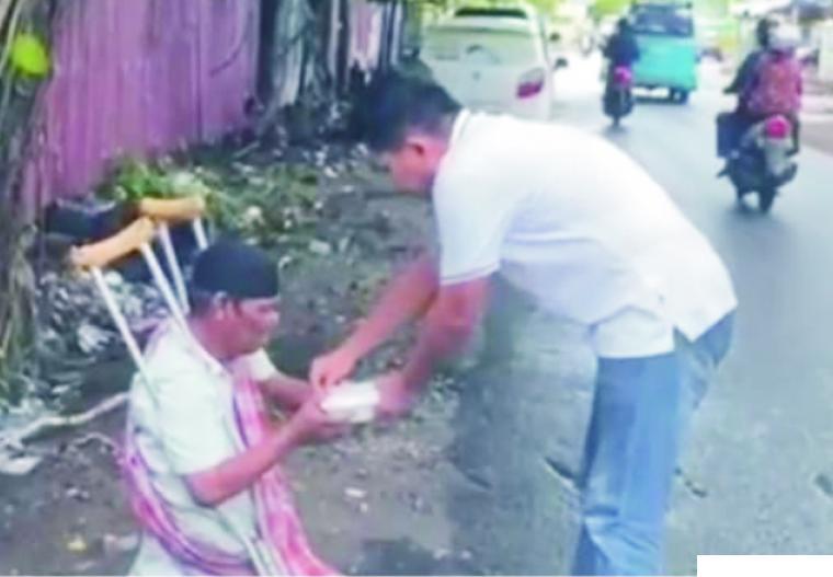 Salah seorang masyarakat yang mendapat sedekah makanan Jumat Berkah bersama Pempek Ampera Tunggul Hitam. PATH
