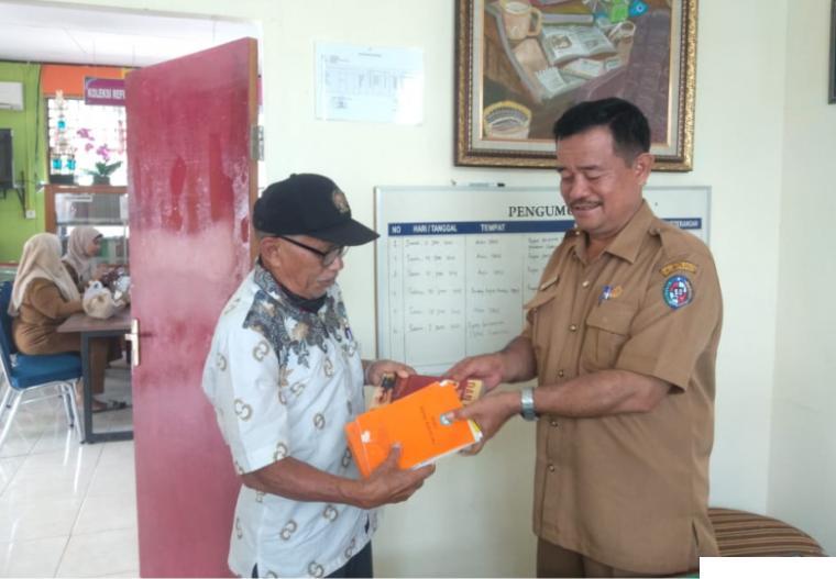 Wartawan senior Syafril Nita menyerahkan buku yang disumbangkannya kepada Kepala Dinas Perpustakaan dan Arsip Kabupaten Limapuluh Kota, Drs. Radimas. IST