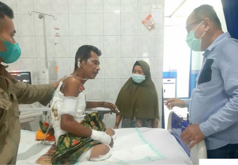 Saril (49 tahun) petani sawit yang tersengat listrik PLN setelah menjalani operasi amputasi pada kedua kakinya di RSUP M. Djamil Padang, Sabtu (31/08/2021). Anggota DPRD Kabupaten Pessel Novermal Yuska (kanan) membezuk Saril. IST