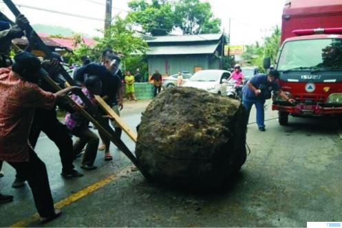 Petugas dari BPBD dan juga warga bersama-sama mengevakuasi batu yang jatuh ke badan Jalan Raya Padang-Painan di Bungus Teluk Kabung, Minggu (27/09/2020). BABARITO