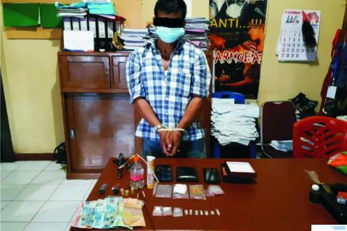 Tersangka AR (51) bersama barang sabu-sabu yang diduga akan dijualnya dan barang-barang lainnya yang diamankan polisi dari warga Naras I, Kecamatan Pariamatan Utara, Kota Pariaman tersebut. TNS