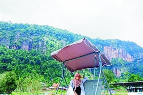 Salah seorang wisatawan berpose dengan latar belakang keindahan alam objek wisata Lembah Harau beberapa waktu lalu. NET