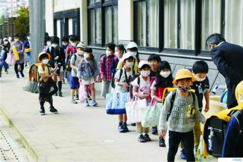 Anak-anak di Jepang disiplin memakai masker. Jepang berhasil menekan angka penyebaran Covid-19 sehingga grafiknya kini sudah landai. NET