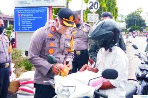 Kapolres Solok Kota, AKBP Ferry Suwandi, SIK memberikan bantuan masker dan sembako kepada keluarga terdampak ekonominya akibat corona, Kamis (09/04/2020).