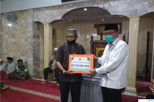 Ketua DPRD Sumbar menyerahkan bantuan Rp20 juta secara simbolis kepada Ketua Pengurus Masjid Baitul Mukmin Payakumbuh, H.Misral, Minggu (18-04-2021) malam. ERZ