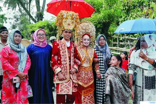 Pasangan mempelai Eby dan Deby didampingi keluarga saat pesta pernikahan di Nagari Inderapura, Kecamatan Pancung Soal, Kabupaten Pesisir Selatan, Sumatera Barat, Sabtu (16/01/2021). Di nagari ini ada yang istimewa. Mempelai pria atau marapulai juga dipasangkan suntiang. HARIYANTO