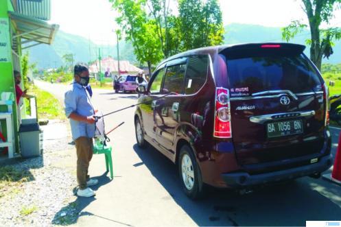 Penyemprotan disinfektan pada kendaraan yang akan memasuki objek wisata Lembah Harau. Pemkab Limapuluh Kota secara resmi akan mulai membuka Lembah Harau bagi kunjungan wisatawan, Minggu (14/06/2020). NITA