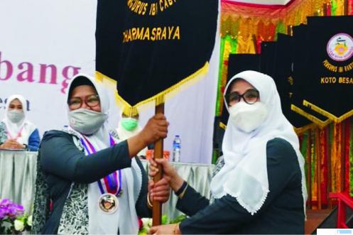 Ketua PD IBI Sumbar, Hj. Hasnawati, SKM, MM menyerahkan pataka kepada Ketua IBI Dharmasraya terpilih Muliati dalam Muscab IBI IV Kabupaten Dharmasraya. DI