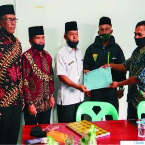 Pj. Wali Nagari Gunung Medan, Jonedy, menyerahkan SK kepengurusan kepada Ketua Pasar Rusdianto, yang disaksikan oleh Ketua KAN dan tokoh masyarakat. (di)