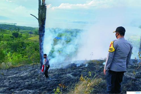 Jajaran kepolisian dari Polres Solok Kota turut membantu memadamkan api yang membakar bukit Puncak Tamudo Muaro Pingai Solok, Rabu (12/08/2020) sore. JON