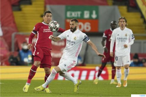 Pemain Liverpool Roberto Firmino (kiri) mengawal striker Real Madrid, Karim Benzema (tengah) dalam laga perempat final Liga Champions, Kamis (15-04-2021) dinihari WIB di Anfield, markas Liverpool. Pertandingan berakhir 0-0 dan Madrid melaju ke Semifinal, karena unggul agregat setelah menang di kandang 3-1. DETIK