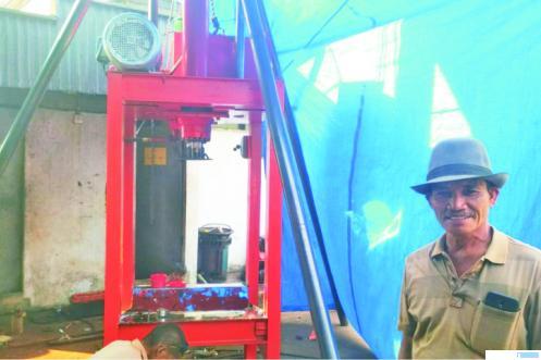 Sabri Dt. Hitam, pengusaha gambir dari Jorong Talang, Nagari Talang Maur, Kabupaten Limapuluh Kota dengan latar alat pres gambir hidrolik elektrik yang sedang dibuatnya sendiri. ERZ