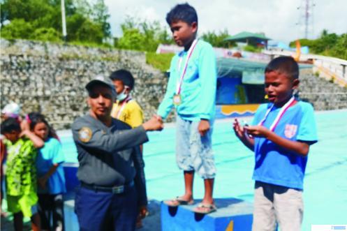 Ketua Bidang Pendanaan PRSI Sumbar, H. Husen, mengalungkan medali emas kepada atlet renang dalam ajang uji coba di SWP Kota Solok. DI