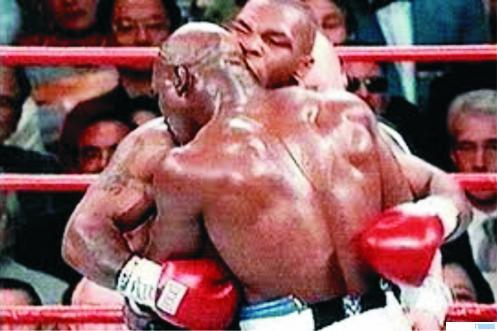 Mike Tyson saat menggigit kuping Evander Holyfield pada pertarungan tahun 1997 lalu. Tyson baru-baru ini mengaku untung besar, pasca peristiwa menggigit kuping Holyfield itu. NET