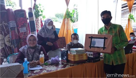 Sekretaris Panitia Syafri Deni menunjukan hadiah laptop yang disumbangkan Joni Hendri dan juga hadiah lain sumbangan berbagai pihak. ERZ